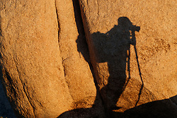 Photographer and rock formations at White Tank, Joshua Tree National Park, California, USA.