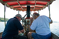 "John Winn of Adingdon, England and Clem LeGates of Milton, Delaware check the map as they navigate the ""Phoenix"" with her 5-horsepower engine and copper plated firebox stoked and ready to steam from Lees Mill in Moultonboro to 19 Mile Bay in Tuftonboro on Wednesday with their fellow steamboaters.  (Karen Bobotas/for the Laconia Daily Sun)"