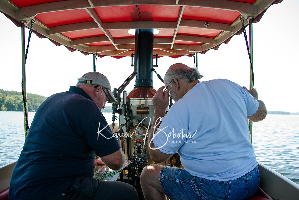 """John Winn of Adingdon, England and Clem LeGates of Milton, Delaware check the map as they navigate the """"Phoenix"""" with her 5-horsepower engine and copper plated firebox stoked and ready to steam from Lees Mill in Moultonboro to 19 Mile Bay in Tuftonboro on Wednesday with their fellow steamboaters.  (Karen Bobotas/for the Laconia Daily Sun)"""