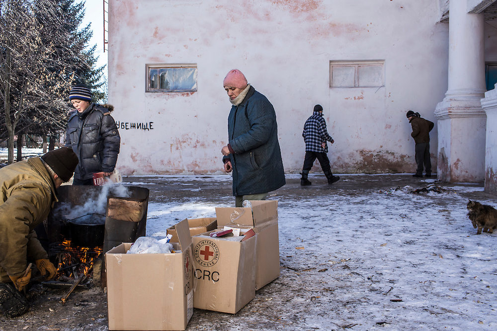 MYRONIVSKYI, UKRAINE - FEBRUARY 17: People cook lunch over a fire outside the local House of Culture, which serves as a distribution point for humanitarian aid and provides a bomb shelter, on February 17, 2015 in Myronivskyi, Ukraine. A ceasefire agreed to by Ukraine and pro-Russian rebel forces has failed to prevent fighting in the nearby town of Debaltseve, where thousands of Ukrainian troops remain and whom rebels claim to have surrounded. (Photo by Brendan Hoffman/Getty Images) *** Local Caption ***