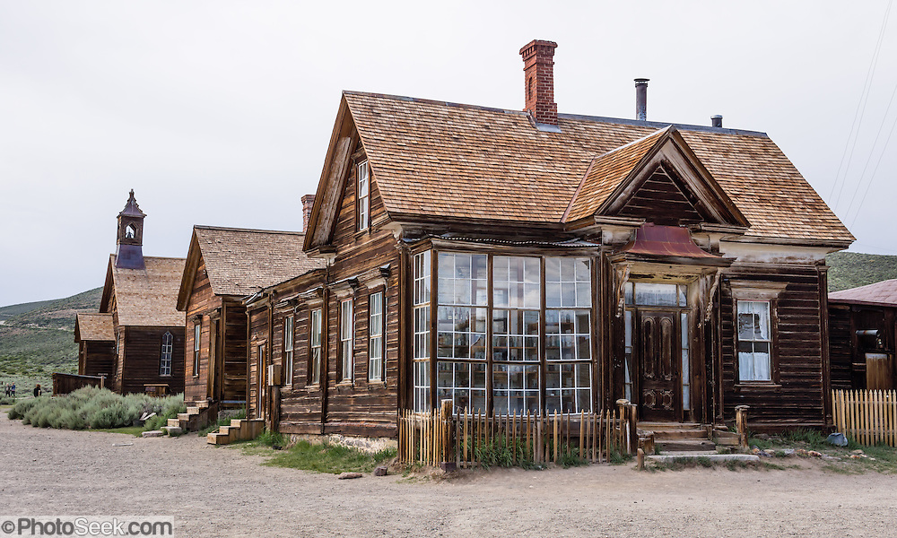 "Prominent windows front the home of James Stuart Cain, who was eventually the principal property owner in Bodie, which is now California's official state gold rush ghost town. Jessie McGath built this house for his new wife in 1879. In the 1890s, JS Cain bought it to live there with his wife until the 1940s. Cain moved to Bodie when he was 25 and built an empire starting with putting lumber barges on Mono Lake and transporting timber to support mine shafts, stoke boilers for machinery, build & heat buildings, and cook food. Cain and a business partner leased a block of land from the Standard Consolidated Mining Company which yielded $90,000 in gold in just 90 days. Cain eventually took control of the Stamp Mill though court action and went on to be one of the richest men in town. Bodie State Historic Park lies in the Bodie Hills east of the Sierra Nevada mountain range in Mono County, near Bridgeport, California, USA. After W. S. Bodey's original gold discovery in 1859, profitable gold ore discoveries in 1876 and 1878 transformed ""Bodie"" from an isolated mining camp to a Wild West boomtown. By 1879, Bodie had a population of 5000-7000 people with 2000 buildings. At its peak, 65 saloons lined Main Street, which was a mile long. Bodie declined rapidly 1912-1917 and the last mine closed in 1942. Bodie became a National Historic Landmark in 1961 and Bodie State Historic Park in 1962."