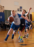 Gilford's Jonathan Mitchell dribbles around Sanbornton's Philip Nichols during the Senior Boys division game of the 21st annual Francoeur Babcock Basketball Tournament  Friday evening.  (Karen Bobotas/for the Laconia Daily Sun)