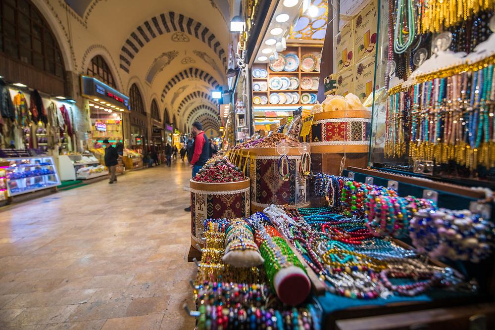 A market stall off of main avenue of Istanbul Spice bazaar in Turkey showcases various bracelets and other brightly colored jewelry items available for purchase