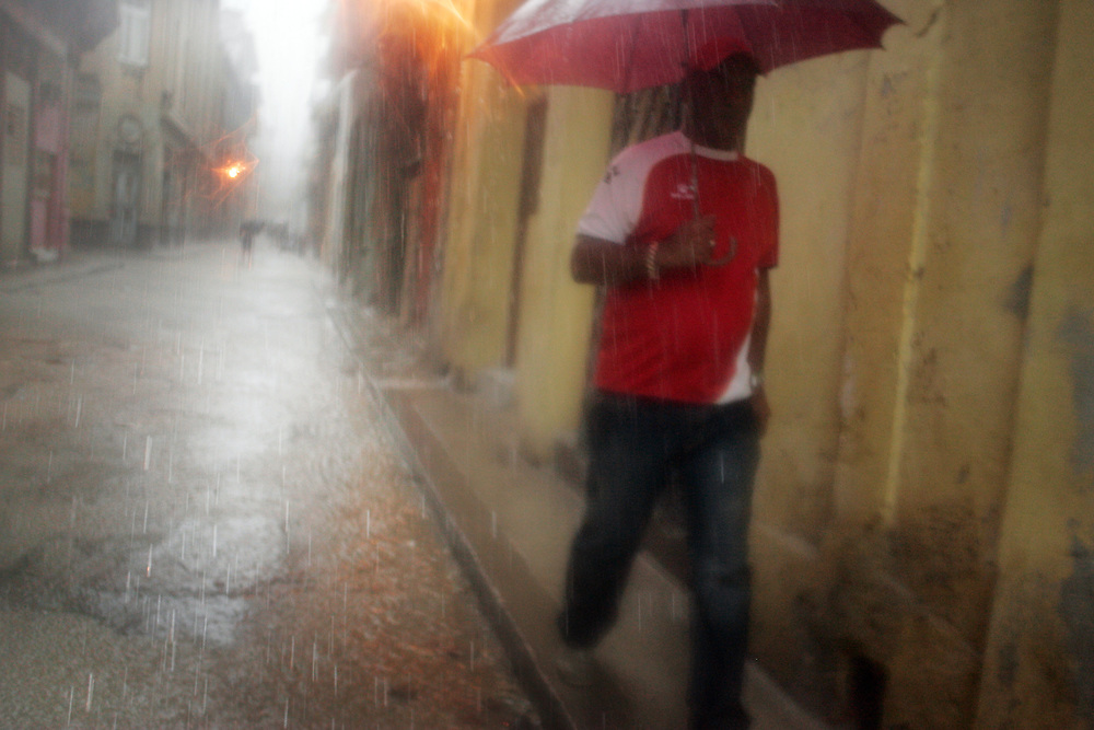 A man walks down a street in Old Havana during a shower of rain.