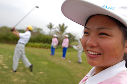 Young female golf caddy watches as golfer tees off on golf course in southern China