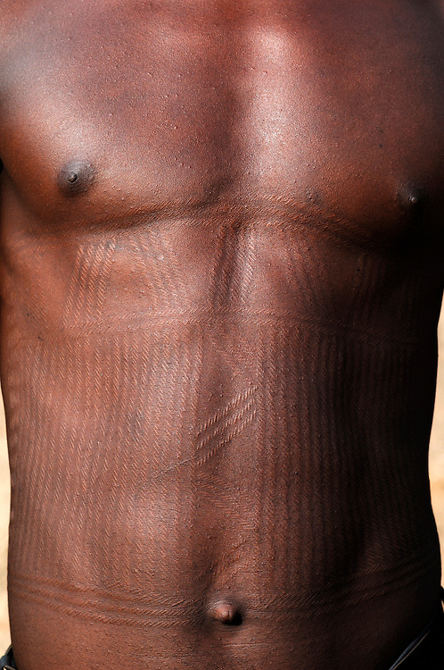 Benin, Natitingou April 22, 2005 - Young man with scarifications on his body. These scarifications represent the passage at the adulthood