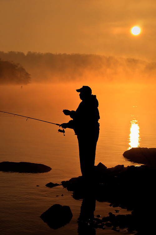 Silhoutte of a fisherman at sunrise on the Susquehanna River, just below the Conowingo Dam, Conowingo, Maryland in late November