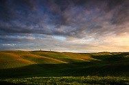 Some beautiful clouds in the sky at sunrise in the rolling hills surrounding the medieval town of San Quirico d'Orcia in Valdorcia, Tuscany, Italy