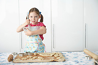 Girl (5-6) preparing cookies in kitchen