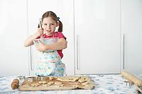 Girl (5-6) preparing cookies in kitchen