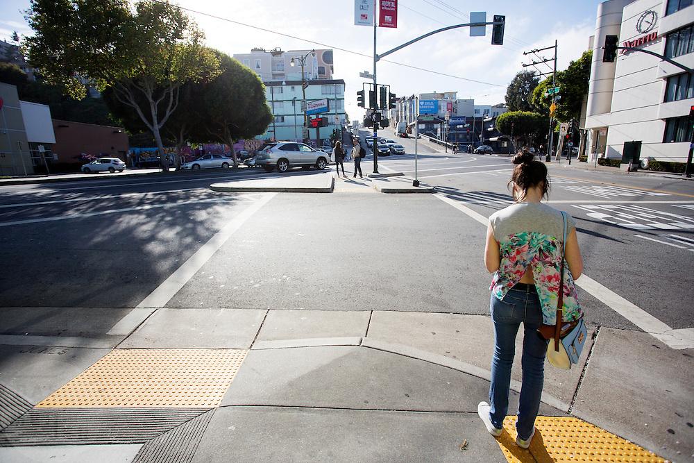 Een vrouw wacht bij een kruispunt in San Francisco, haar shirt waait iets op. De Amerikaanse stad San Francisco aan de westkust is een van de grootste steden in Amerika en kenmerkt zich door de steile heuvels in de stad.<br /> <br /> The US city of San Francisco on the west coast is one of the largest cities in America and is characterized by the steep hills in the city.