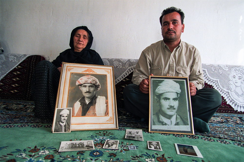 Sef Abdullah (left) and her son Amjad Badin Mohammad holding pictures of male family members &quot;disappeared&quot; by Saddam Hussein's regime during his &quot;Anfal&quot; campaign.  In 1982-83 the regime rounded up an estimated 200,000 Kurds who have never been seen since. Sef Abdullah lost her husband, six of her seven sons and her two sons-in-law. Her youngest son, Amjad Badin Mohammad, is the only male survivor of her family.<br /> Hamdela, Iraqi Kurdistan. 16/11/2002.