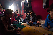 CALAIS, FRANCE - JAN 16: Refugees from Afghanistan play cards inside a makeshift shelter in the Calais refugee camp known as the 'jungle' on January 16, 2016.