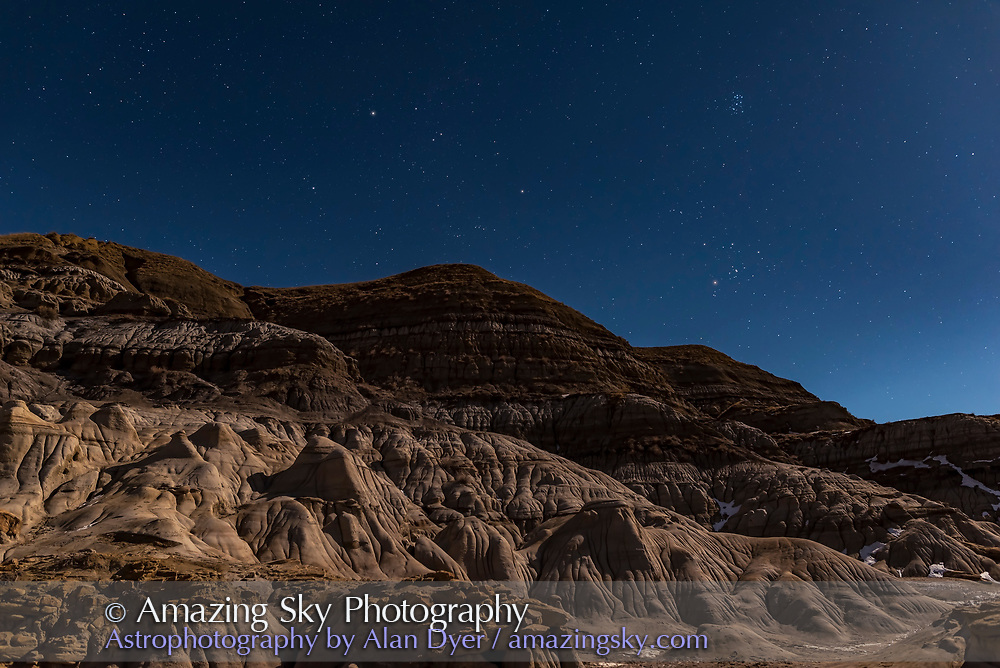Auriga (at left) and Taurus (at right) rising in the moonlight at the Hoodoos near Drumheller, Alberta. Illumination is from the waxing gibbous Moon. <br /> <br /> This is a stack of 4 exposures for the ground to smooth noise, and one for the sky, all 10 seconds at f/2.8 with the 24mm lens and Nikon D750 at ISO 800.