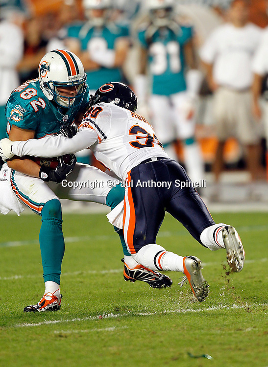 Miami Dolphins wide receiver Brian Hartline (82) gets hit after catching a pass by Chicago Bears cornerback D.J. Moore (30) during the NFL week 11 football game against the Chicago Bears on Thursday, November 18, 2010 in Miami Gardens, Florida. The Bears won the game 16-0. (©Paul Anthony Spinelli)