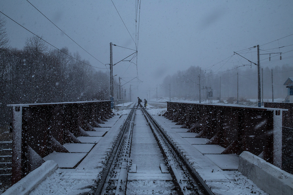People cross train tracks during a snowstorm on Sunday, October 20, 2013 in Baikalsk, Russia.