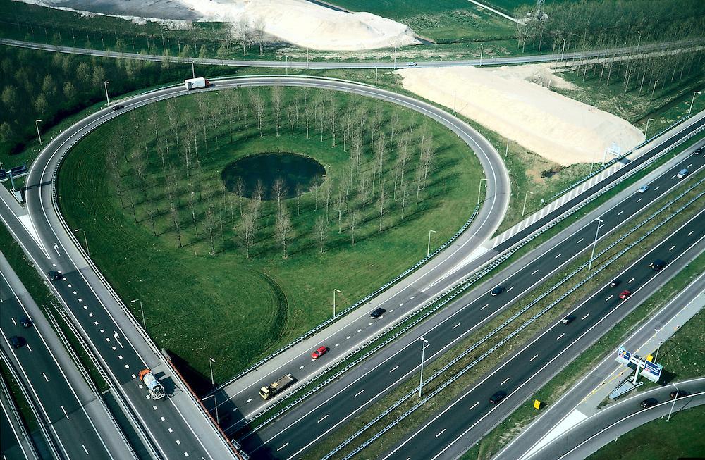 Nederland, Gelderland, Knooppunt Deil, 04-04-2002;  Noordoostelijk kwadrant verkeersknooppunt  (met hoofdrijbaan naar Rotterdam, links en idem naar Utrecht, rechts); de Betuweroute kruist het knooppunt aan de Noordzijde, zand voor dijklichamen van het toekomstige viaduct ligt in te klinken; klaverblad met populieren in het overhoekse gebied; vrachtvervoer verkeer en vervoer milieu .Deel van een serie over Betuweroute / infrastructuur.