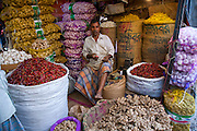 A vendor sells potatoes, ginger, garlic and chili at a market in Dhaka, Bangladesh.