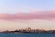 San Francisco skyline at sunset as seen from the water with sailboat.
