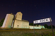 The large railroad sign identifying the small town of Big Rock, IL to passing trains is across the tracks from the town's small grain elevator complex.