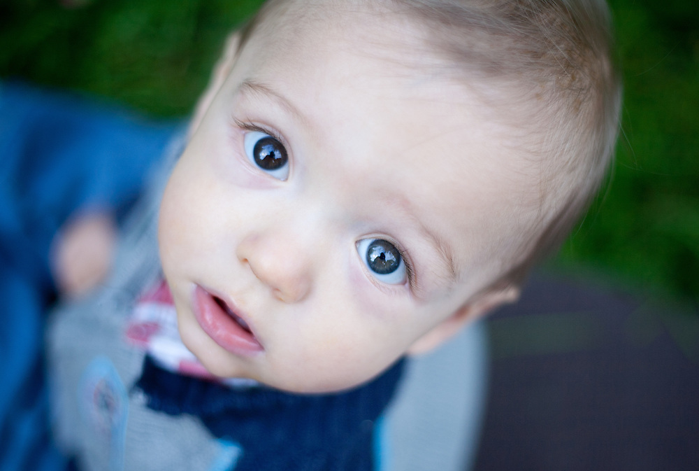 Portraits of a baby boy playing by himself outside on a blanket in a grassy area