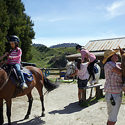 Youngsters are prepared for horse trekking with Paradise Valley Ventures Horse Riding near Rotorua.  Paradise Valley Ventures Horse Riding is set on 700 acres of New Zealand pasture, a working farm with sheep and cattle. Paradise Valley, Rotorua, New Zealand.  New Zealand. 10th December 2010. Photo Tim Clayton.