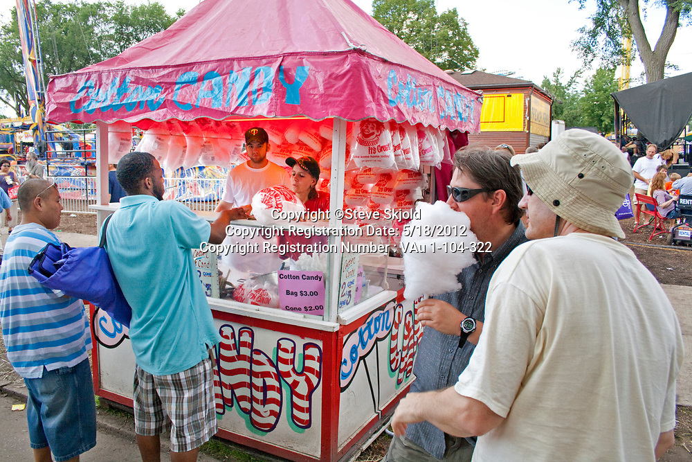 People buying cotton candy in an artistic concession booth.  Minnesota State Fair St Paul Minnesota MN USA