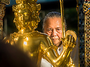 "04 SEPTEMBER 2015 - BANGKOK, THAILAND: PHRAMAHARAJAGURUPHITISRIVISUTTHIKUN, the Royal Priest of Thailand, blesses the Four Faced Brahma statue at the Erawan Shrine during a rededication ceremony Friday. A ""Holy Religious Ceremony for Wellness and Prosperity of our Nation and Thai People"" was held Friday morning at Erawan Shrine. The ceremony was to regain confidence of the Thai people and foreign visitors, to preserve Thai religious customs and traditions and to promote peace and happiness inThailand. Repairs to Erawan Shrine were completed Thursday, Sept 3 after the shrine was bombed on August 17. Twenty people were killed in the bombing and more than 100 injured. The statue of the Four Faced Brahma in the shrine was damaged by shrapnel and a building at the shrine was damaged by debris.    PHOTO BY JACK KURTZ"