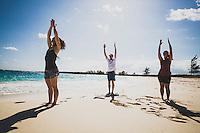 Brian White, Elizabeth White and Jacki Arevalo dig into for a little impromtu beach yoga, Lee Stocking Cay, Exumas, Bahamas.