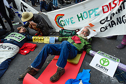 © Licensed to London News Pictures. 10/10/2019. LONDON, UK. Pensioner activists Sylvia Boyle (L) and Brian Larkin (R) secured by plastic pipe, lay on the ground in Trafalgar Square during day 4 of Extinction Rebellion's climate change protest in the capital.  Activists are calling on the Government to take immediate action against the negative impact of climate change.  Photo credit: Stephen Chung/LNP