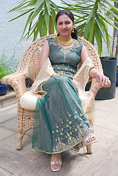 Woman wearing traditional Asian dress sitting in a chair smiling,