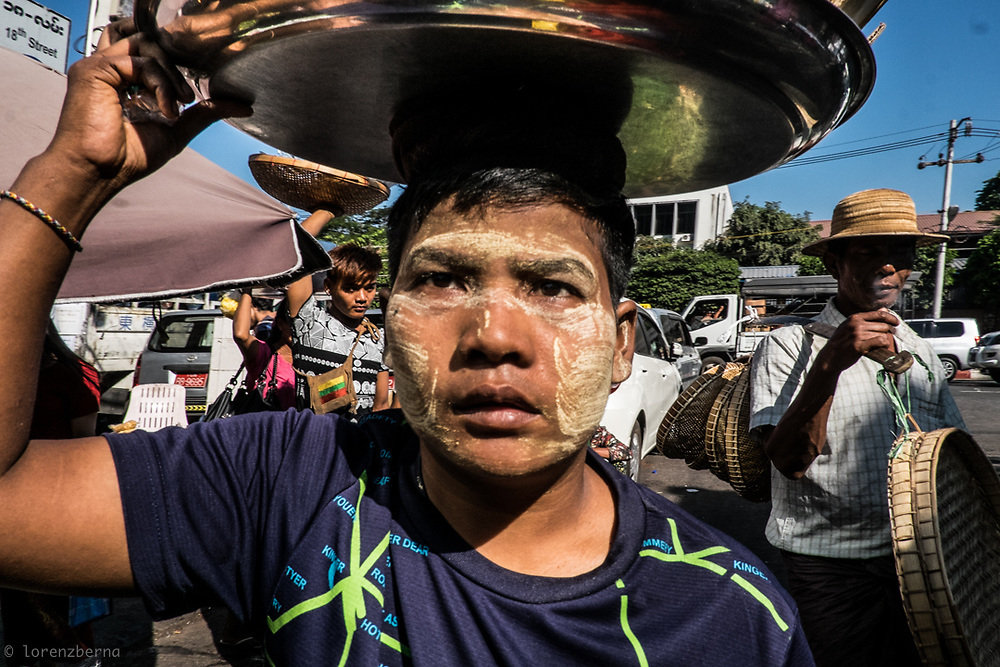 Thanaka wood paste on her face, shield this street vendor from the harsh sun of the tropic in Yangon, Myanmar.<br />