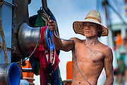 30 APRIL 2013 - MAHACHAI, SAMUT SAKHON, THAILAND:   A Burmese crewman operates a winch on a Thai fishing trawler in Mahachai, Samut Sakhon province, Thailand. The Thai fishing industry is heavily reliant on Burmese and Cambodian migrants. Burmese migrants crew many of the fishing boats that sail out of Samut Sakhon and staff many of the fish processing plants in Samut Sakhon, about 45 miles south of Bangkok. Migrants pay as much $700 (US) each to be smuggled from the Burmese border to Samut Sakhon for jobs that pay less than $5.00 (US) per day. There have also been reports that some Burmese workers are abused and held in slavery like conditions in the Thai fishing industry.         PHOTO BY JACK KURTZ