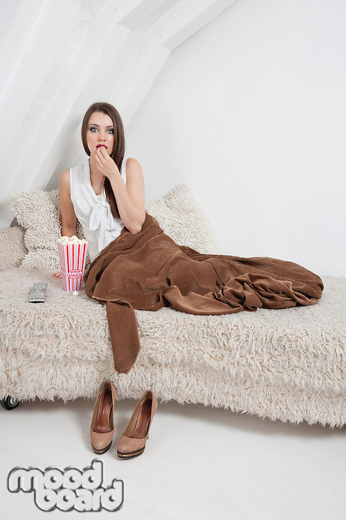 Portrait of young woman sitting on bed and eating popcorn