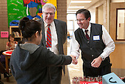 Volunteers Neil Wilkinson and Roland Radack, center and right, greet a shopper during the Deseret Media Corporation sponsored Toy Depot for selected families at Washington Elementary, Monday, Dec. 3, 2012.