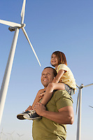 Father and daughter (5-6) on wind farm side view