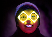 Young girl with glowing glasses.Black light