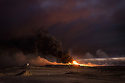 Smoke billows from one of the burning oil wells, spreading toxic fumes over vast areas and exposing large numbers of civilians to the harmful chemicals present in the smoke from burnt crude oil. On windy days the smoke spreads throughout the area, blanketing the nearby town of Qayyarah, often blocking out the sun for days at a time.