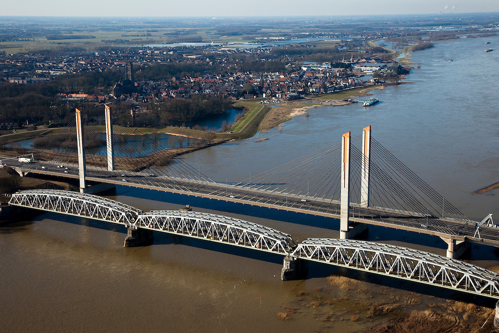 Nederland, Gelderland, Zaltbommel, 07-03-2010; bruggen over de rivier de Waal, gezien naar de Bommelerwaard met Zaltbommel in de achtergrond. Voorgrond de spoorburg (spoorlijn Utrecht - Den Bosch), tweede plan de Martinus Nijhofbrug (rijksweg A2). De oude brug voor autoverkeer is gesloopt (pijler nog in de rivier)..Bridges over the River Waal, in the direction of the Bommelerwaard and Zaltbommel. First the railway bridge (railway line Utrecht - Den Bosch), second the Martinus Nijhof bridge right (A2). The old traffic bridge has been demolished (pillar still in the river)..luchtfoto (toeslag), aerial photo (additional fee required).foto/photo Siebe Swart