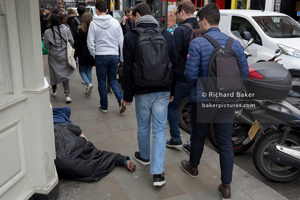 Passers-by walk past a homeless man whose hand is stretching across the pavement in Great Newport Street, on 16th April 2018, in London, England.