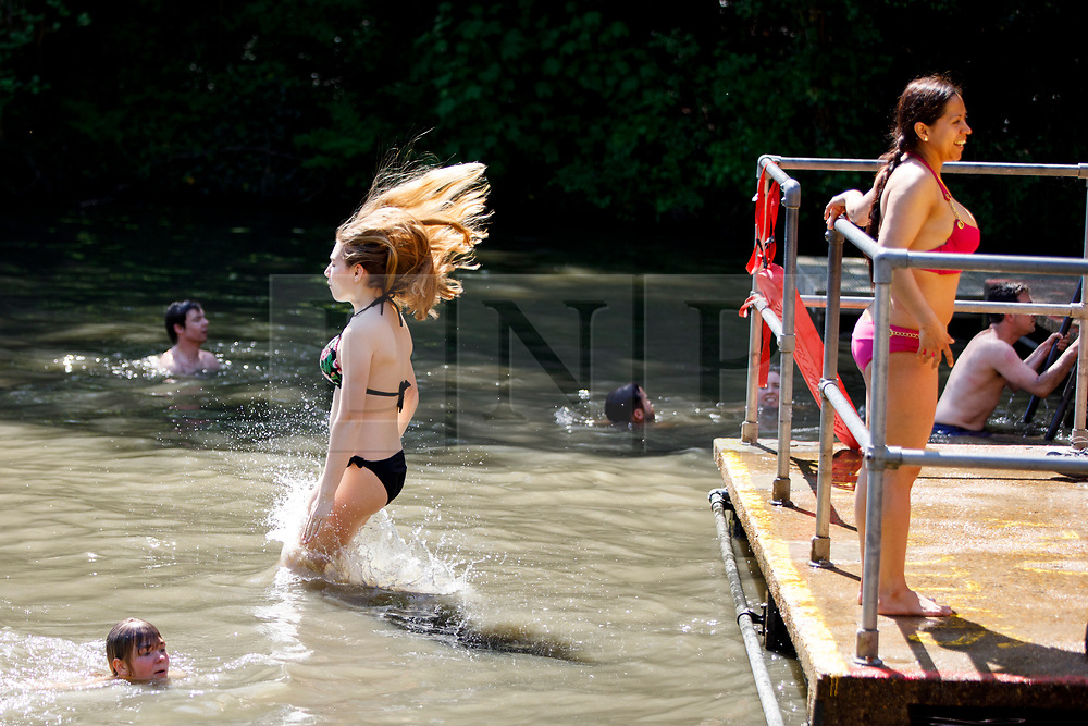 © Licensed to London News Pictures. 07/05/2018. London, UK. People swim in Hampstead Heath Mixed Bathing Pond in north London as temperatures hit 28C on the hottest May bank holiday since 1999 on Monday, May 7, 2018. Photo credit: Tolga Akmen/LNP