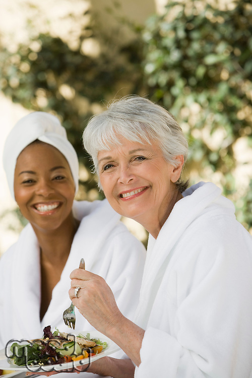 Portrait of women in bathrobes eating at health spa