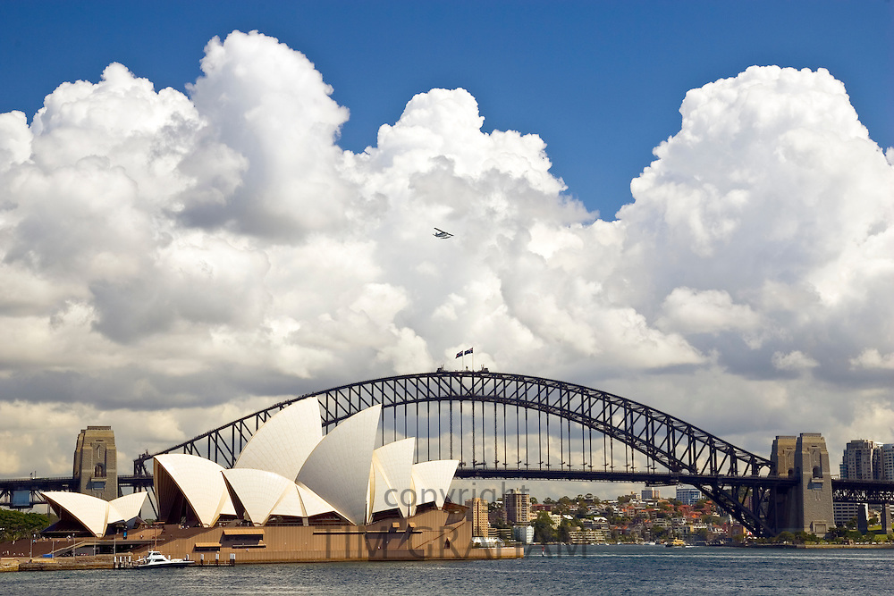Sydney Opera House and Sydney Harbour Bridge with small plane flying over, Australia