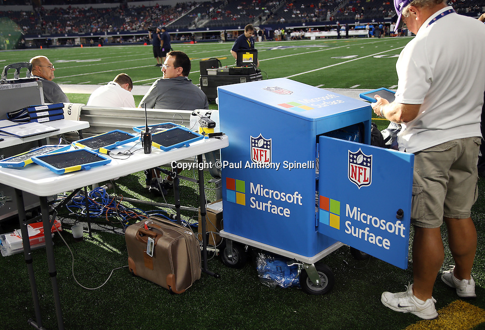 Workers set up the sideline game tablets before the Dallas Cowboys 2015 NFL preseason football game against the Houston Texans on Thursday, Sept. 3, 2015 in Arlington, Texas. The Cowboys won the game 21-14. (©Paul Anthony Spinelli)