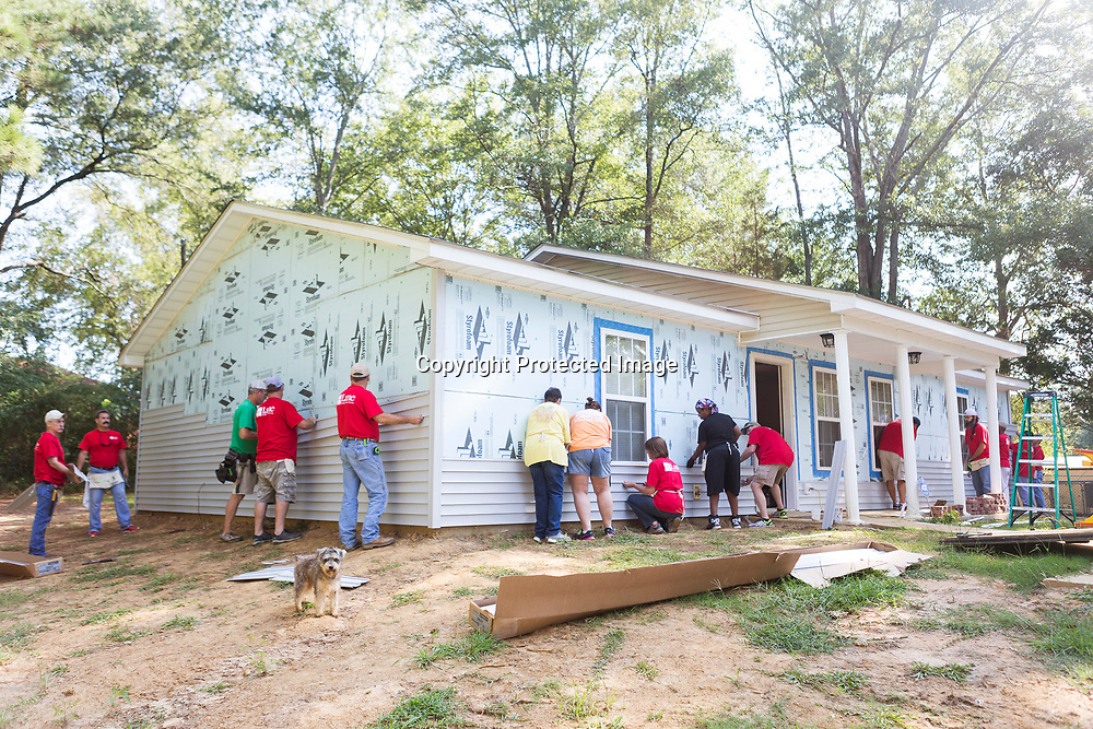 Lane Furniture employees and other volunteers work on attaching the siding to a Habitat for Humanity home Friday morning in Verona.