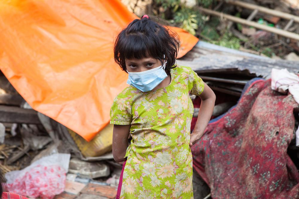 Meisje met gezichtsmasker te midden van de puinhopen van het huis van haar familie in de stad Sakhu, nabij Kathmandu.
