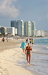 10 Feb 2014. Cancun, Mexico.<br /> Lady in a bikini walks the tourist beach at Isla Cancun along the Zona Hotelera on the Carribean Sea. <br /> Photo; Charlie Varley/varleypix.com