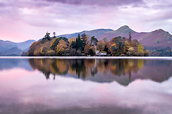 © Licensed to London News Pictures. 06/11/2019. Keswick UK. The sky turns pastel pink at dawn this morning as the mountains & Derwent Isle reflect in to the still water of Derwentwater in Keswick this morning in Cumbria. Photo credit: Andrew McCaren/LNP