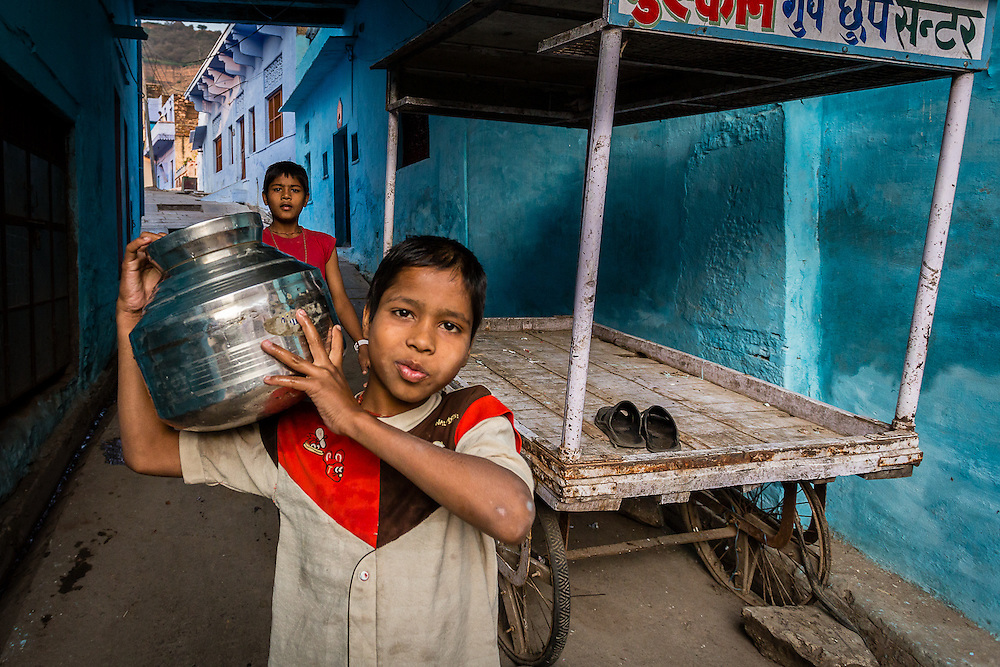 Two brothers leave their home, in a blue alley, to fetch some water or milk.