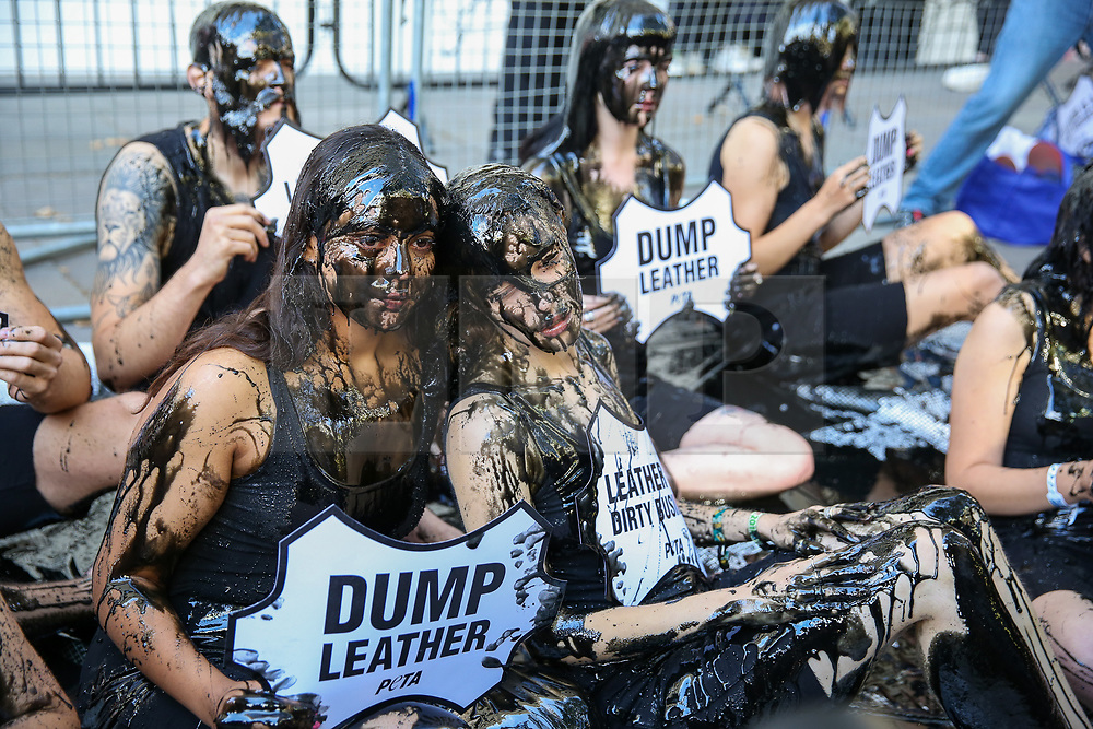 "© Licensed to London News Pictures. 13/09/2019. London, UK. The campaigners from People for the Ethical Treatment of Animals (PETA) protests against the hazardous waste associated with the leather industry are covered in black ""toxic slime"" on the opening day of London Fashion Week. Photo credit: Dinendra Haria/LNP"
